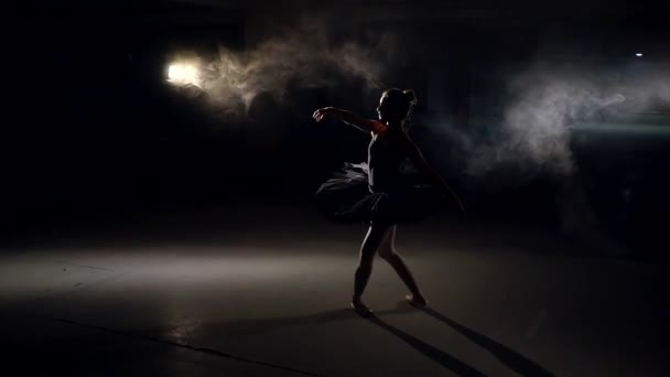 silhouette of dancing ballerina with hair in a bun, in huge empty gloomy hall