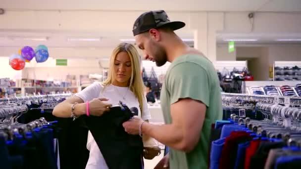 a930ac8ba634 En ung man och en vacker kvinna välja sport byxor för fru, damen håller  kläder– stockfilm