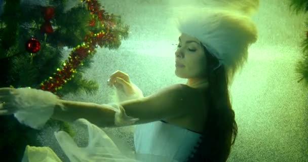 hó leány úszik a víz alatt közel karácsonyfa lassított felvétel