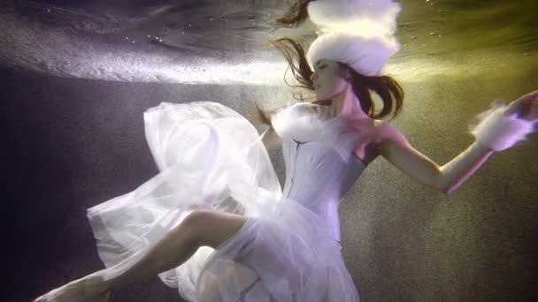 Sněhová panna s šifónovou sukní plave pod vodou zpomaleným pohybem