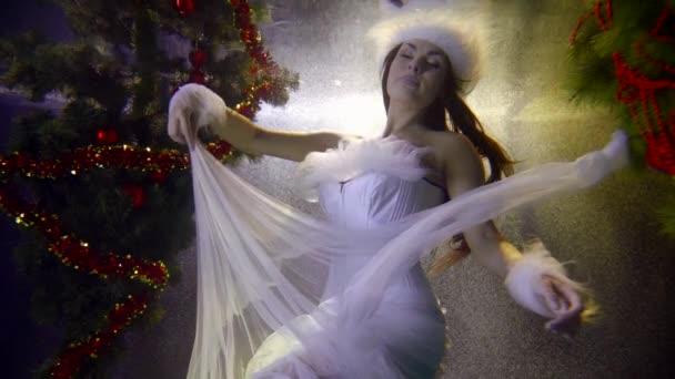 Schneemädchen schwimmt in der Nähe von Weihnachtsbaum unter Wasser Zeitlupe
