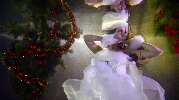 krásná bruneta s dlouhými vlasy v bílých šatech s bílou kožešinou a bílým kožešinovým kloboukem se vznáší v proudu bublin mezi vánočními stromky pod vodou. bílé světlo obrysu. tmavá klávesa
