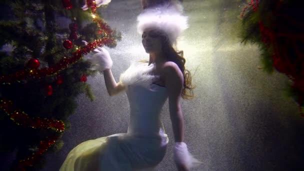 Silhouette einer Frau in weißer Kleidung mit weißem Pelz und weißer Pelzmütze in einem Blasenstrom zwischen Weihnachtsbäumen unter Wasser. Konturweißes Licht. dunkler Schlüssel