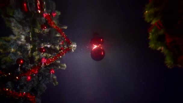 Nový rok slavnostní zelené umělé vánoční stromky s míčky a věnce jsou pod vodou na tmavém pozadí close-up, vedle vzlétá plave červený vánoční míč.