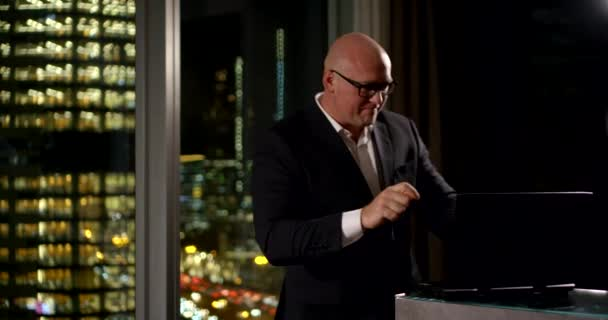 Šťastný plešatý obchodník v černém obleku a brýlích tančí za laptopem, který stojí na pultu v bytě, za ním panoramatické okno, ve kterém svítí světla města.