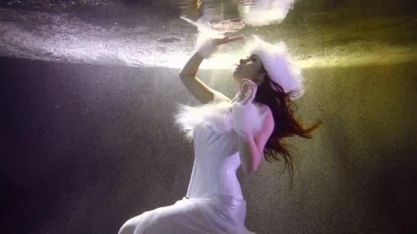 ein schönes Mädchen in einem weißen Neujahrskleid, sie ist unter Wasser und schwimmt in ihr Spiegelbild hinauf, auf ihrem Kopf trägt sie einen weißen flauschigen Hut und an ihren Händen flauschige Armbänder.