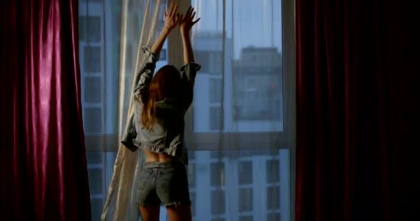 szexi nő táncol egyedül a szobában előtt nagy ablak este, vetkőzés
