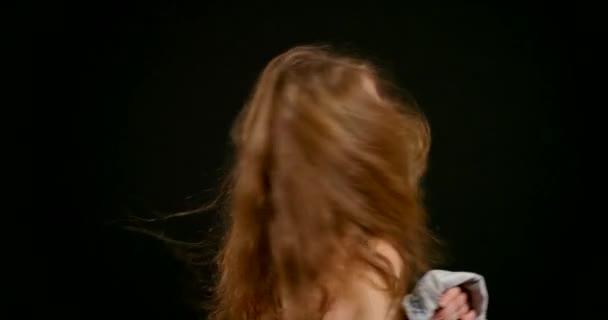 Porträt einer schönen Blondine auf schwarzem Hintergrund. Sie zieht eine Jeansjacke an, justiert ihren Kragen. Lange Haare flattern. Durchschnittlicher Plan