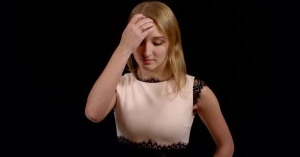 egy komoly, figyelmes lány portréja csipkés ruhában. Belenéz a kamerába és kiegyenesíti a haját. fekete háttér