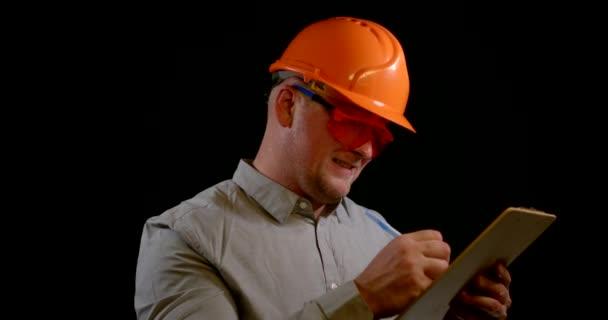 portrét veselého muže v šedé košili a oranžové přilbě a brýlích. něco napíše na tablet, podívá se do kamery, usměje se a pokračuje v psaní poznámek. černé pozadí