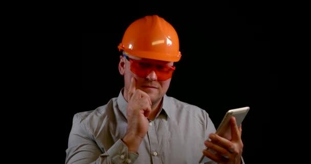 Seriöser Ingenieur mit orangefarbenem Helm auf Tablet-Großaufnahme