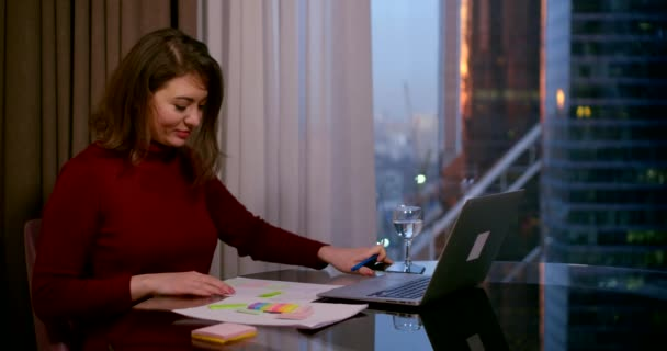 close - up of a brunette in a Burgundy dress. she sits at a round table near a window. she checks her smartphone, smiles, starts writing, thinks. behind the window you can see city buildings