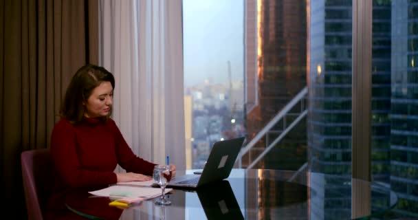Egy nő ül az irodájában egy üzleti központ egy asztalnál, előtte van egy laptop, egy pohár, ír valamit egy toll egy darab papírt, a háttérben egy ablak és felhőkarcolók.