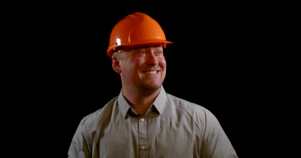 šťastný a úspěšný stavitel nosí oranžovou ochrannou přilbu, stojí, zvedá palce nahoru