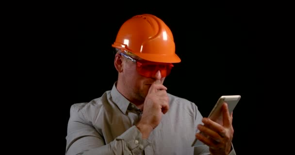 Polier mit Schutzhelm und Brille kommuniziert per Tablet, tippt auf Touchscreen