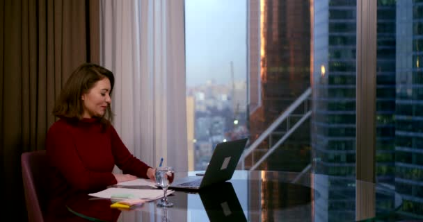 a woman in a Burgundy dress sits at a round table near a large window. she communicates through a video link on a laptop and makes recordings. behind the window you can see high-rise city buildings
