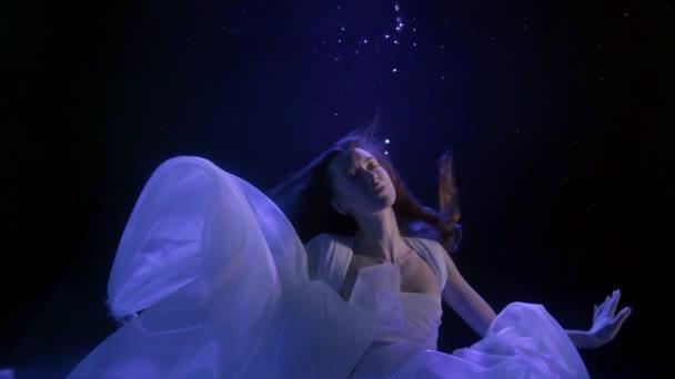ve tmě pod vodou se vznášela krásná bruneta s dlouhými vlasy. zvedne a spustí ruce. modré světlo obrysu