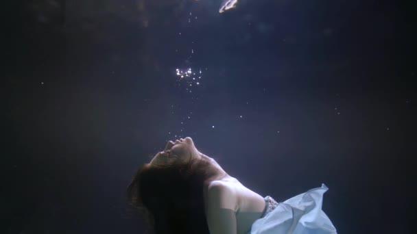 portrét tváře v profilu tmavovlasé dívky s kamínky na tváři, která je pod vodou, jemnou látkou šatů a rozvíjejícími se vlasy. Odráží se to od hladiny vody.