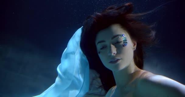 Frau mit Feen-Make-up aus Edelsteinen taucht in klarem Wasser Nahaufnahme