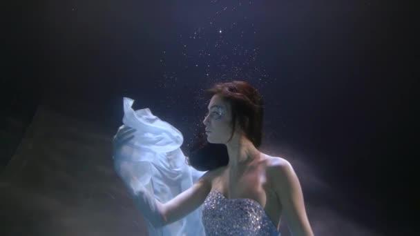 tajemná mladá žena hraje s světle modrým šifón tkaniny pod vodou v bazénu
