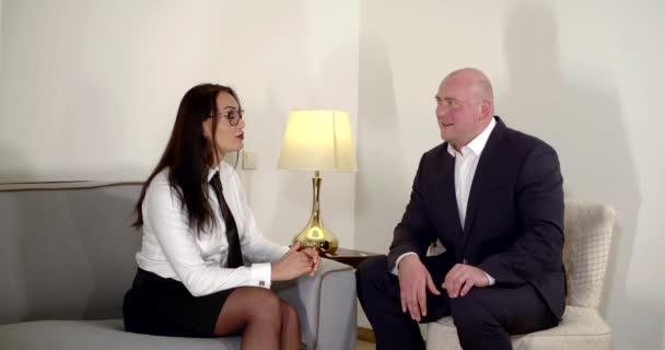 žena v brýlích a muž v obleku sedí u zářící lampy. žena něco řekne a gestikuluje. muž se zájmem naslouchá