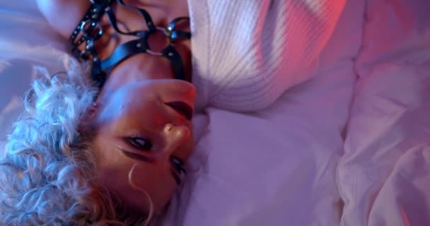 Porträt einer Blondine mit hellem Make-up. Sie trägt schwarze Ledergürtel und einen weißen Pullover. Scheiben liegen auf den Laken. die Aussicht von oben. Nahaufnahme. blaues und rosa Licht