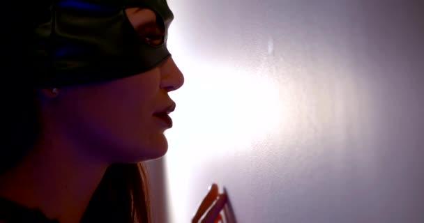 sexuelle Frau mit schwarzer Leder-Katzenmaske für BDSM-Spiel, Berührung der Wand mit den Fingern