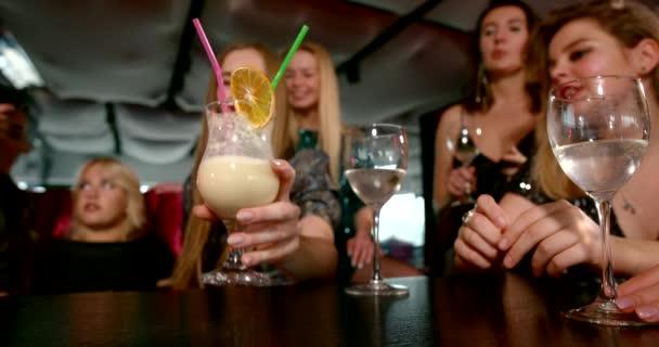 Freundinnen ruhen sich auf Party im Restaurant aus, die Hand reicht zum Glas