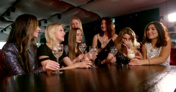 joyful women are celebrating bachelorette party in restaurant, toasting and clinking glasses