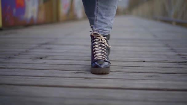 Detailní záběr ženských nohou v džínách a černých botách s krajkovými podpatky, kráčejí po dřevěném mostě, v pozadí zeď s nápisy.