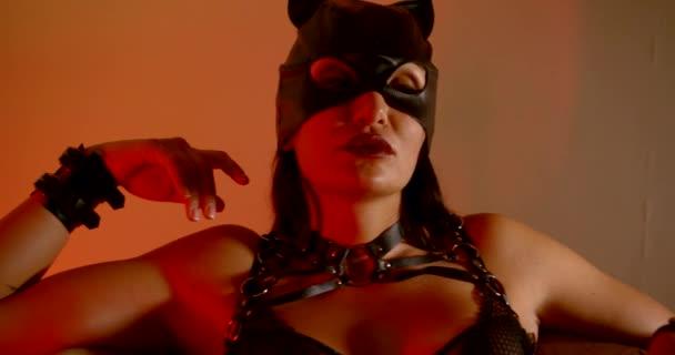 Nahaufnahme eines dunkelhaarigen Mädchens mit Catwoman-Maske in einem erotischen sexy Lederanzug und mit Kragen.