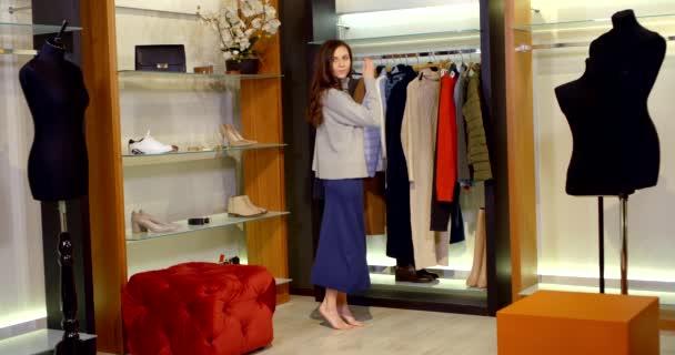 Portrét krásné ženy v obchodě s oblečením. Mladá brunetka s červenými rty v obchodě s oblečením. Vybrala si sukni a svetr. Módní žena ve stylovém oblečení