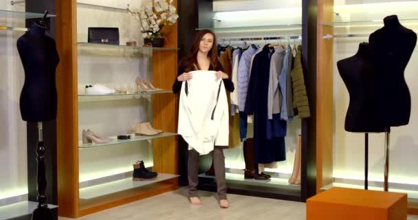 Ta holka nakupuje. Krásná žena v obchodě s oblečením. Vybrala si kalhoty a košili, kterou si vyzkoušela. Módní žena ve stylovém oblečení