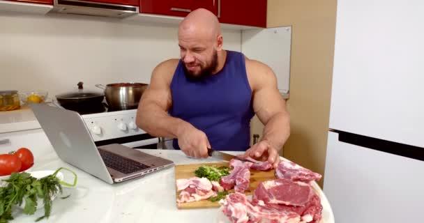 bulliger Mann schneidet Fleisch und schaut am Laptop Kino, sitzt am Wochenende allein in der Küche