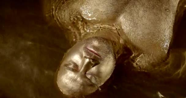 Portrét svalnatého plešatého muže ležícího ve vodě pokrytého kovovým zlatým prachem. Meditace s ponořením pod vodu. Děsivý, šílený pohled muže