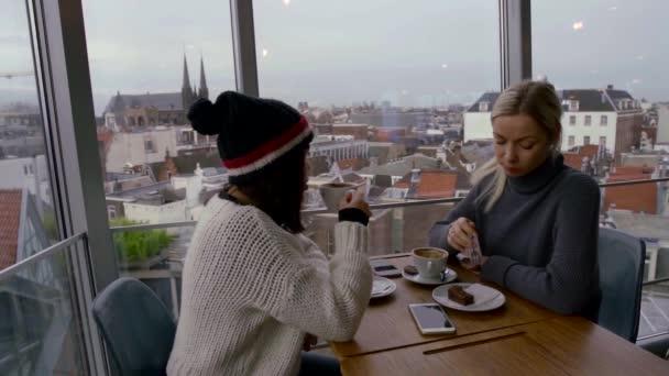 barátok ülnek egy kávézóban, közel egy nagy ablakhoz. A szőke tortát eszik. Egy barna nő kalapban a fején kávét iszik. kommunikálnak. az ablakból látni a régi város