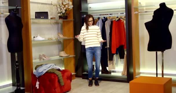 Tmavovlasá štíhlá mladá žena je v dámském šatníku šatny s figurínami a oblečením, zkouší si džíny, pruhovaný bílý svetr, bundu a boty na vrchu.