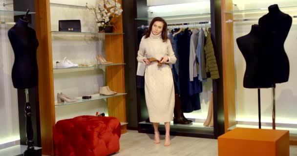 Tmavovlasá mladá štíhlá žena je ve velké dámské šatní skříni s figurínami a různými šaty, botami a vyzkouší si lehký svetr a popruh na něm.