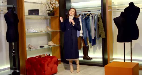 bruneta s dlouhými vlasy je v šatně. žena v tmavomodrém kabátě a béžových vysokých botách. nasadila si náušnice a obdivuje se
