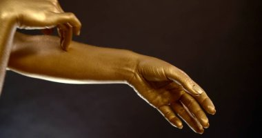 Close-up portrait of womens hands in gold pigment on a black background in the Studio. They make dancing movements.