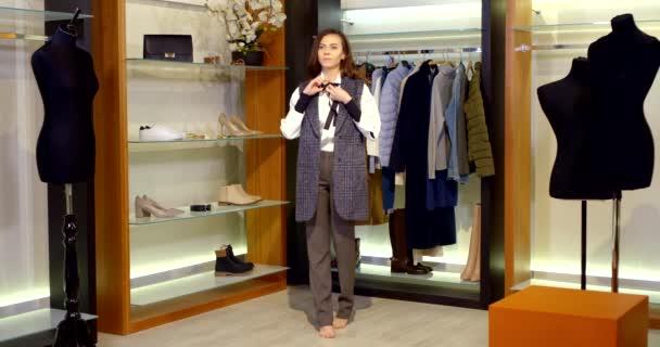 v šatně je bosá brunetka s dlouhými vlasy. žena má na sobě klasické kalhoty, bílou košili a dlouhou vestu. zavazuje si černou kravatu