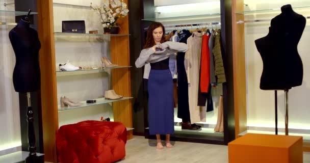 v šatně je bosá brunetka v dlouhé modré sukni. žena si zkouší šedý svetr s velkým límcem