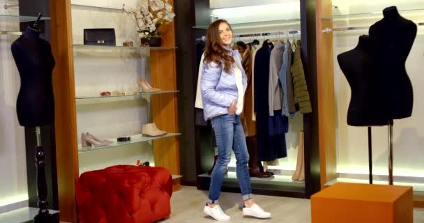 bruneta s dlouhými vlasy je v šatně. žena v bílém svetru, džínách, teniskách a modré bundě. tančí a obdivuje se, pak se začne svlékat
