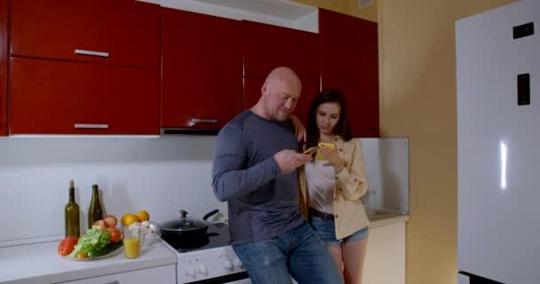plešatý muž a dívka v košili a šortkách, stojí v kuchyni u sporáku v objetí, drží mobilní telefony, mluví, usmívá se. Za nimi je ovoce a zelenina.