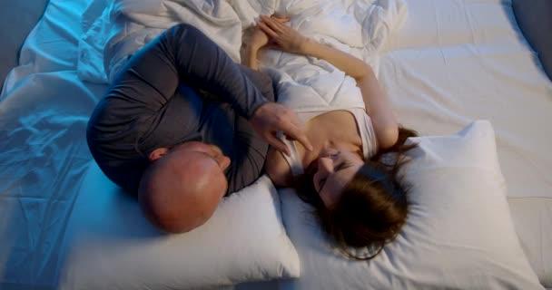 šťastný muž žena mluvit odpočívá ve velké manželské posteli v noci