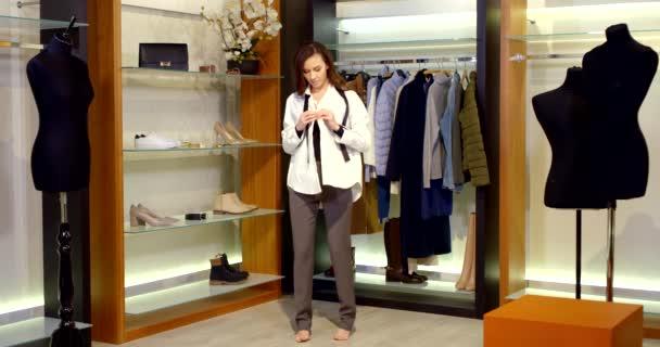v šatně je bosá brunetka s dlouhými vlasy. žena je oblečena do klasických kalhot a zapíná si volnou bílou košili. Černá kravata přehozená přes krk