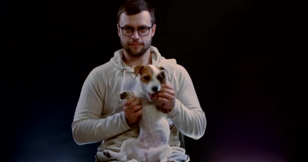Portrait of a dark-haired man with a middle-aged beard, holding his little dog on his lap, scratching his tummy. They are in the Studio on a black background.