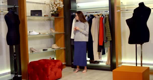 v šatně je bosá brunetka s brýlemi. žena v dlouhé modré sukni a šedém svetru. vybere si a vyzkouší si náušnice