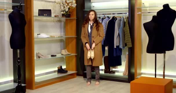 bruneta s dlouhými vlasy je v šatně. žena má na sobě hnědý kabát po kolena a klasické kalhoty. zvedne se a vyzkouší si béžové vysoké podpatky