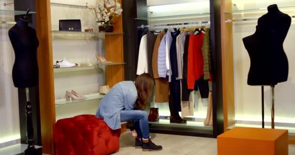 Tmavovlasá štíhlá mladá žena je v dámském šatníku šatny s figurínami a oblečením, vyzkouší si džíny, džínové sako a boty.